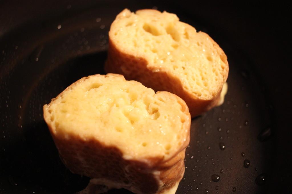 フランスパンのフレンチトーストをフライパンで焼いている画像