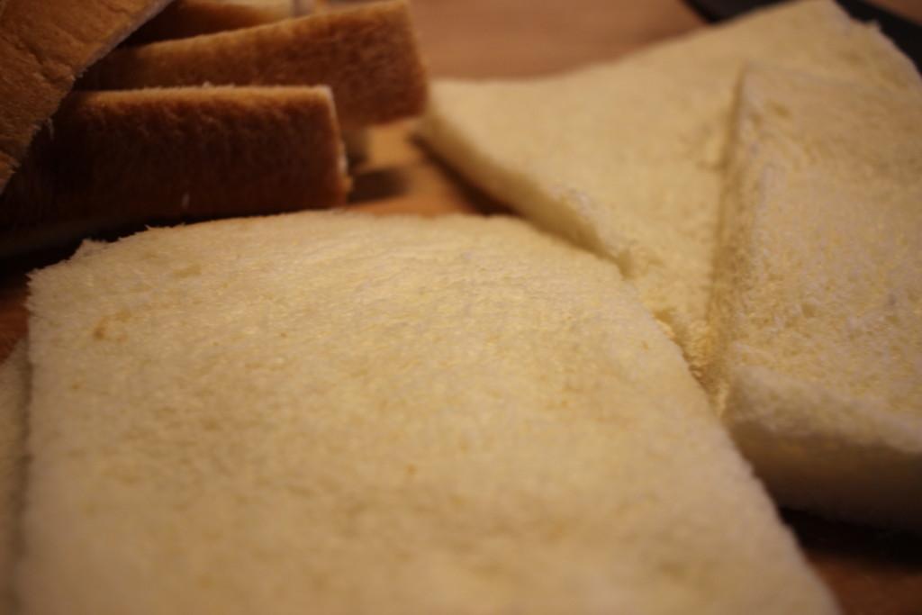 食パンを半分に切っている画像
